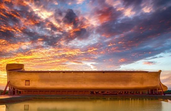 arche de Noé en bois, grandeur nature, devant une étendue d'eau, sous le soleil couchant