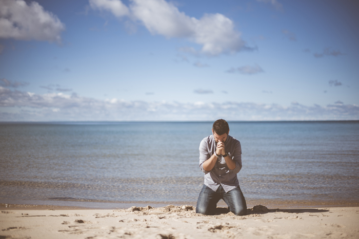 prier dans la nature; homme agenouillé mains jointes en prière, tête inclinée, sur la plage de sable blanc blond, devant la mer calme transparente en fond, sous un beau ciel bleu avec nuages épars