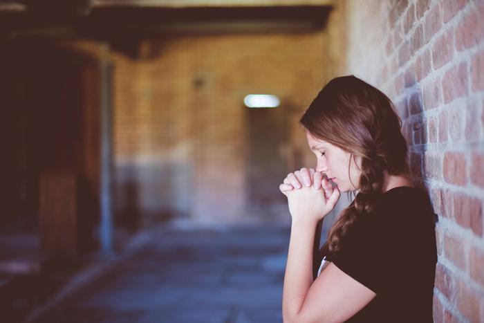 fille, jeune femme priant les yeux fermés adossée à un mur de briques rouges, aux cheveux châtain clair foncé et natte sur le côté, en haut noir manches courtes, les mains jointes en prière, dans un bâtiment église désaffecté