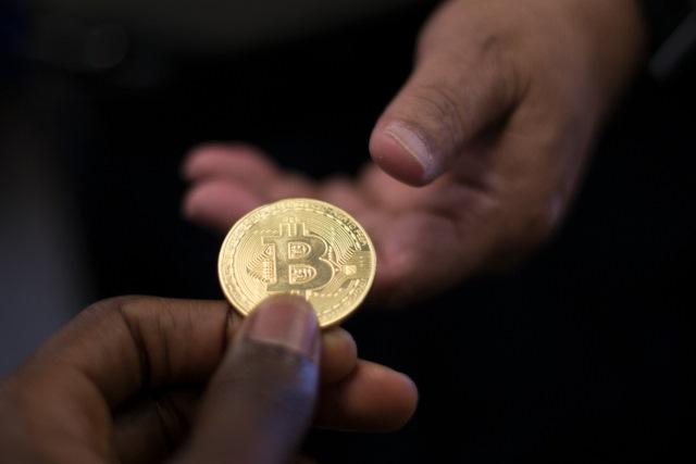 un bitcoin în mâna cuiva