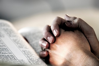 folded hands resting on open Bible