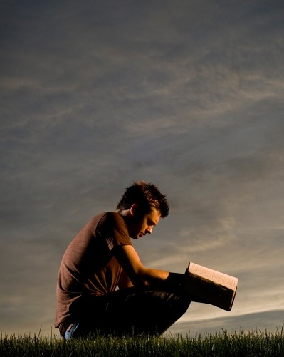 man kneeling in the grass with Bible