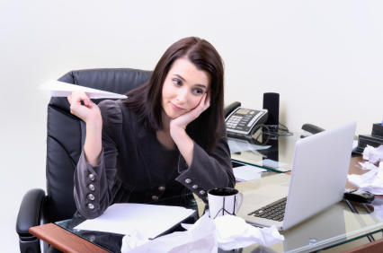 woman sitting at a messy desk, holding a paper airplane (wasting time)