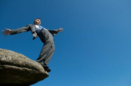 आदमी एक चट्टान के किनारे से गिर जाने वाला है।