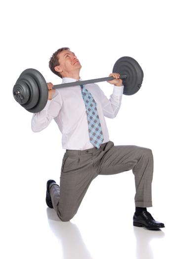 homme en pantalon chemise cravate, soulevant une barre d'haltérophilie trop lourde pour lui, sur un genoux
