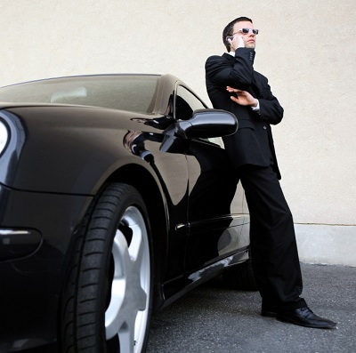 man leaning against expensive car while talking on a cell phone