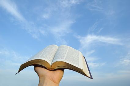Bible ouverte tenue par une main gauche, levée vers le ciel