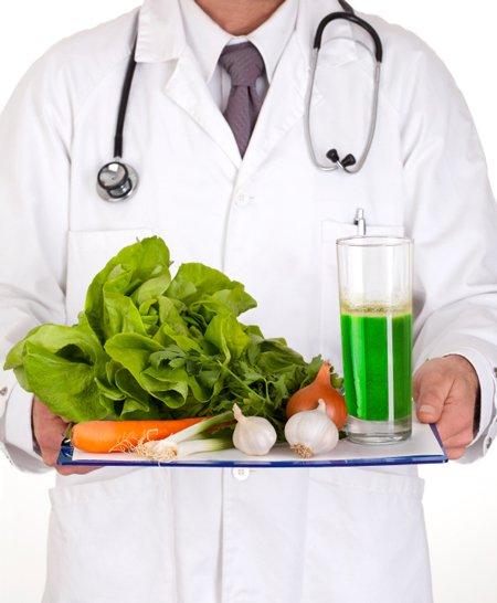 docteur en blouse blanche, un stéthoscope autour du cou, un plateau de jus vert frais de légumes à la main, salade verte, carotte, oignon, ail, poireau