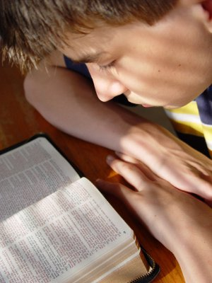 young boy reading Bible
