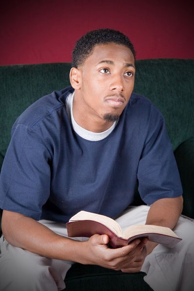 young contemplative man holding Bible