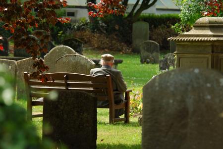 आदमी कब्रिस्तान में बैठे