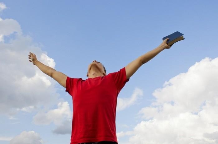 hombre con los brazos levantados al cielo y una Biblia en la mano