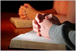 složené ruce spočívající na bibli