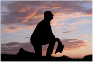 Muž klečí v modlitbě
