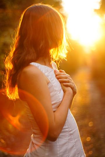 Mladá žena při pohledu zpět při západu slunce