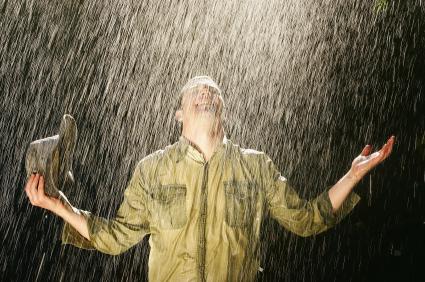 agricultor sonriente de pie bajo la lluvia