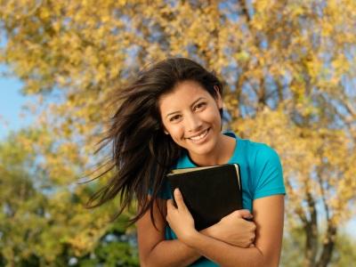 mujer sonriente que sostiene la Biblia