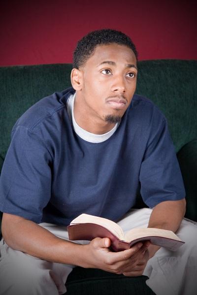 hombre contemplativo joven que sostiene la Biblia