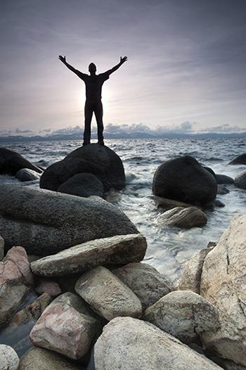 pria yang berdiri di atas batu dengan tangan terangkat