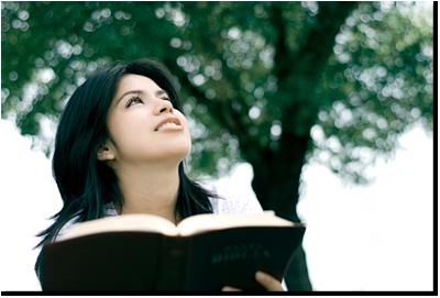 Wanita melihat ke kejauhan sambil memegang Alkitab