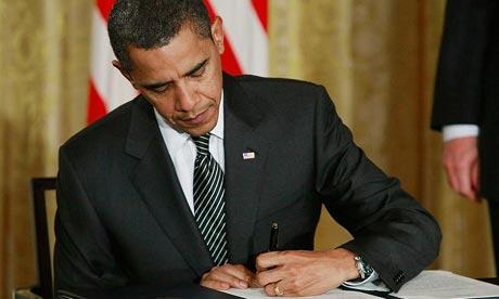 Presiden Obama sedang menandatangani peraturan pemerintah.