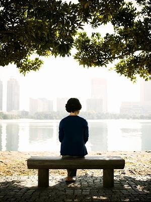 Jong man sit alleen op 'n bank