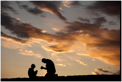 Pria dan anak berlutut dalam doa