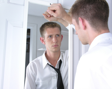 Pria menatap dirinya di cermin