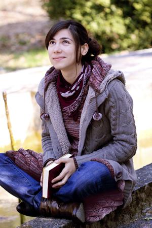 mujer joven que sostiene la Biblia y mirando al cielo