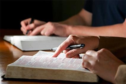dva lidé, kteří studují Bibli