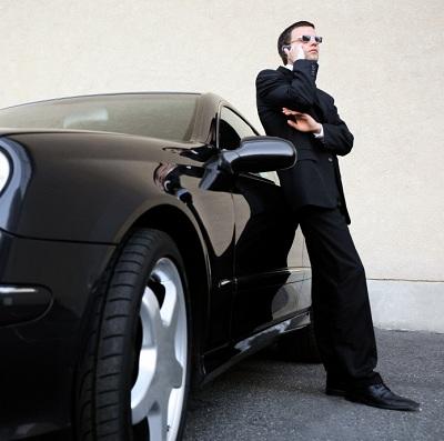 Pria bersandar mobil mahal saat berbicara di ponsel