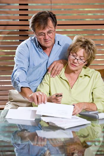 pasangan yang lebih tua melihat dari atas tagihan mereka