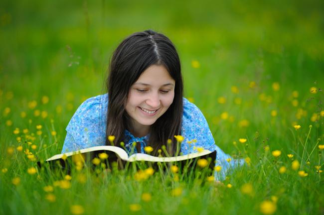 jong glimlaggende meisie wat die Bybel in die natuur lees
