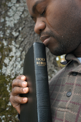 man holding Bible with tears running down his face