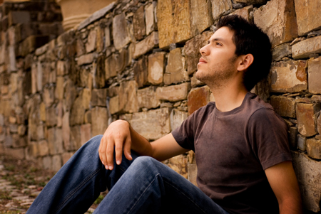 contemplative youn man sitting against a wall