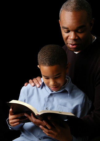 father and son reading Bible together