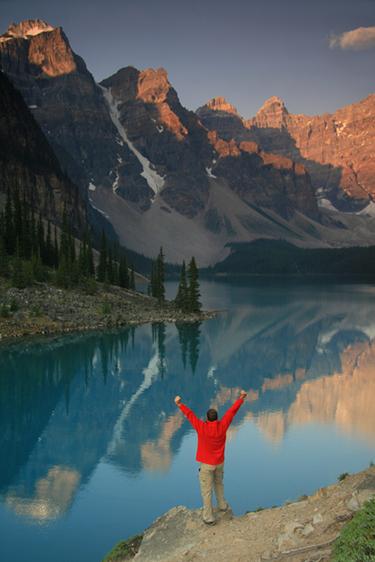 man rejoicing by a lake