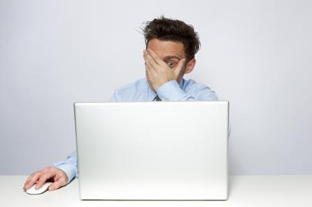 man peeking through hands at a computer screen