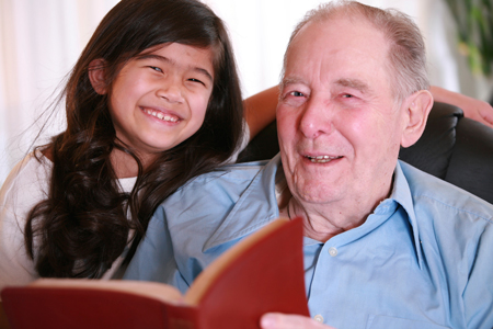 grandfather reading Bible to granddaughter