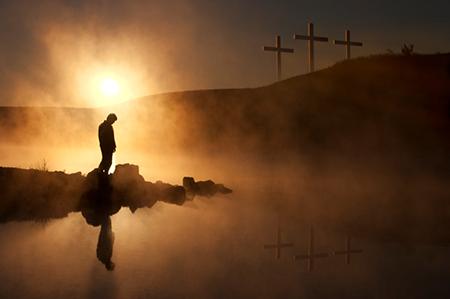 십자가 앞에 회개하는 남자가 서 있는 모습