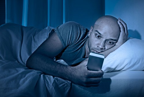man lying in bed staring at cell phone