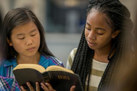 两个女孩阅读圣经
