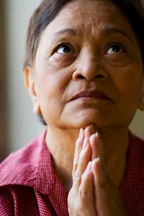 Eine ältere Frau betet