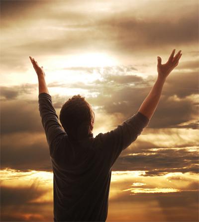 lofprysinge – man met arms omhoog wat na die hemel kyk