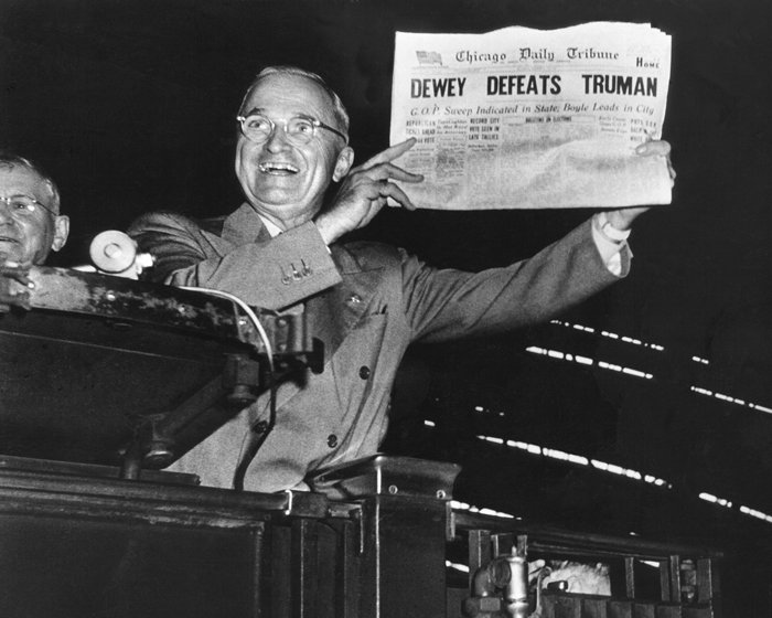 President Truman laughs at a newspaper headline declaring his opponent the winner.