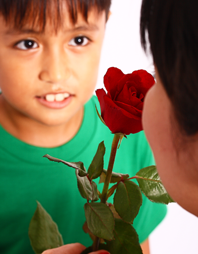 ein Junge überreicht seiner Mama eine Rose