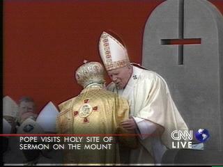 nakaupo sa trono si John Paul II na may nakasaliwang krus