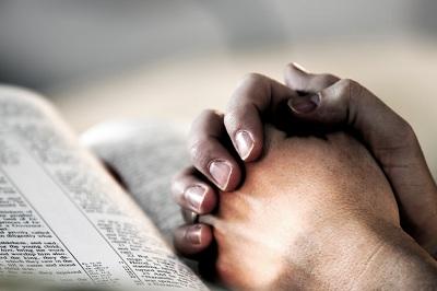 gefaltene Hände ruhen auf einer geöffneten Bibel