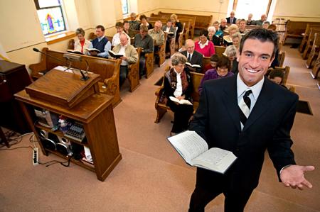 Glimlaggende pastoor met gemeente in die agtergrond