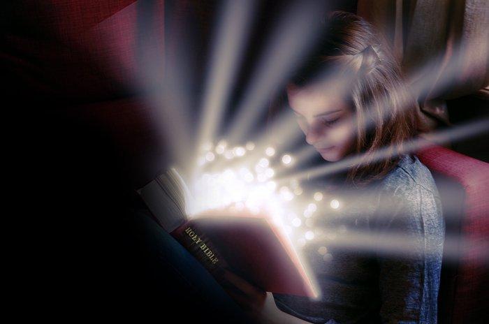 fille lisant la Bible lumineuse; lumière jaillissant de la Bible